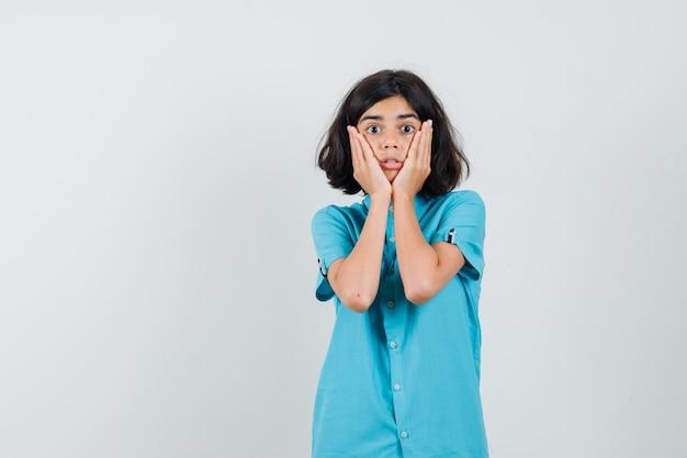 彼女の頬に手をつないで驚いて見える青いシャツの10代の少女