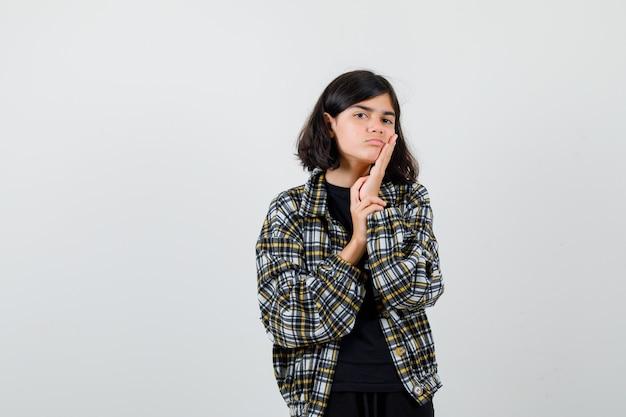 頬に手を保ち、暗い、正面図を探しているカジュアルなシャツの十代の少女。