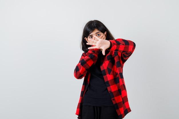 カジュアルなシャツを着た10代の少女は、身を守るために手を上げ、口に手を保ち、ショックを受けたように見えます。正面図。