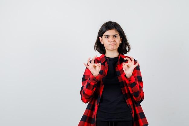 カジュアルなシャツを着た10代の少女は、okのサインを示し、躊躇しているように見えます。正面図。
