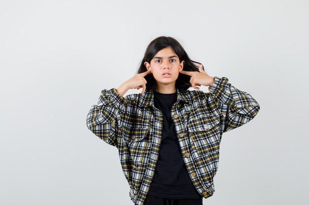 캐주얼 셔츠를 입은 10대 소녀가 귓불을 손가락으로 만지고 쾌활한 표정을 짓고 있습니다.