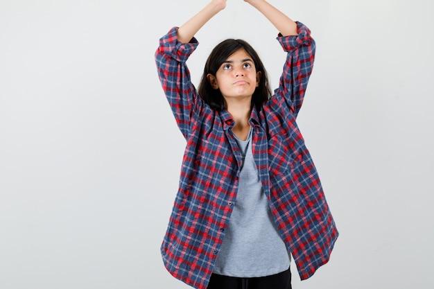 市松模様のシャツを着た10代の少女が、頭上に手をかざして家の屋根のジェスチャーをし、物欲しそうな正面図を探しています。