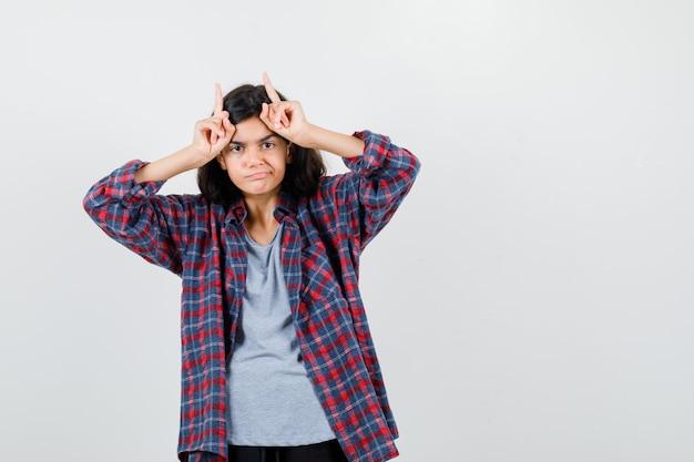 체크 무늬 셔츠를 입은 10대 소녀가 뿔을 보여주고 실망한 모습을 보입니다.
