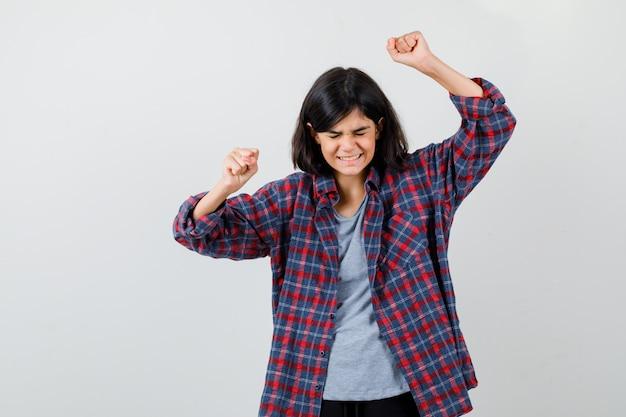 Девушка в клетчатой рубашке показывает жест победителя и выглядит счастливым, вид спереди.