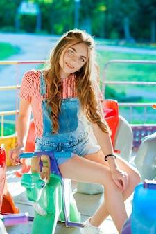 カラフルな服を着て、ブランコに座って抱きしめる十代の少女