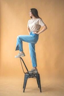 Девушка в джинсовых джинсах и повседневной одежде 90-х, стоя на старом стуле в студии. бежевый фон. естественная поза и стильное дизайнерское фото