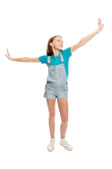 비행 포즈, 전체 높이에서 데님 바지에 십 대 소녀. 흰 배경에 고립