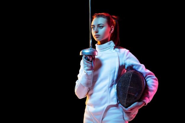 검은 배경, 네온 빛에 고립 된 손에 칼으로 펜싱 의상에서 십 대 소녀.