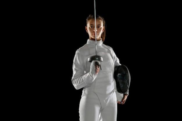 黒の背景に分離された手に剣とフェンシング衣装の十代の少女