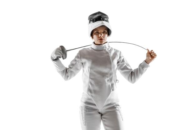 白い背景で隔離の手に剣とフェンシングの衣装を着た10代の少女。
