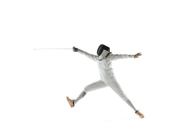 白いスタジオの背景に分離された手に剣とフェンシングの衣装を着た10代の少女。若い女性の白人モデルは、動き、行動の練習とトレーニングをしています。コピースペース。