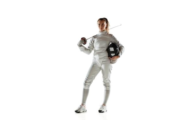 白い壁に分離された手に剣とフェンシングの衣装を着た10代の少女