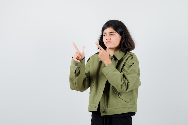 緑のジャケットを着た10代の少女が上を向いて好奇心をそそる、正面図。