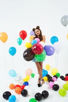 Девочка-подросток в одежде в стиле пин-ап держит букет из воздушных шаров