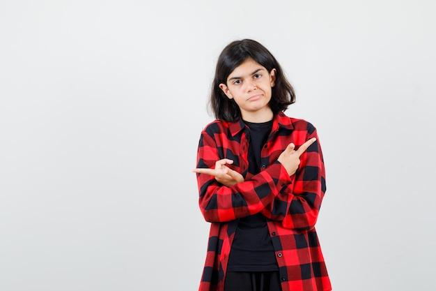 티셔츠를 입은 10대 소녀, 체크무늬 셔츠가 팔짱을 끼고 양쪽을 가리키고 무모한 정면을 바라보고 있습니다.