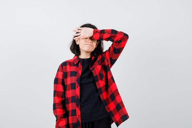 Tシャツを着た10代の少女、額に手を握り、がっかりしているように見える市松模様のシャツ、正面図。