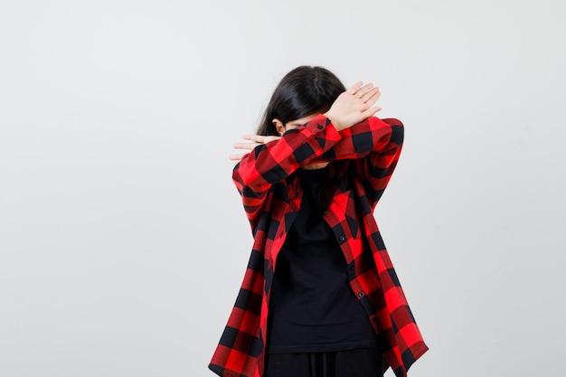 Девушка-подросток в футболке, клетчатой рубашке показывает жест отказа и выглядит уверенно, вид спереди.