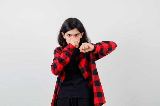 Девушка-подросток в футболке, клетчатой рубашке, стоящей в позе боя и выглядящей уверенно, вид спереди.