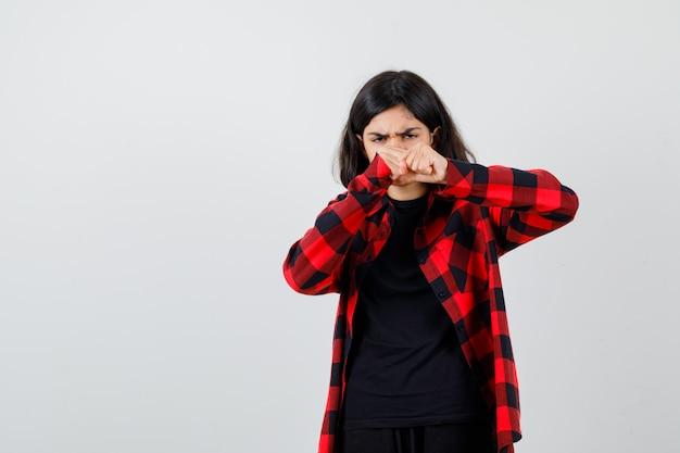 Девушка в футболке, клетчатой рубашке, стоящей в позе боя и серьезной, вид спереди.