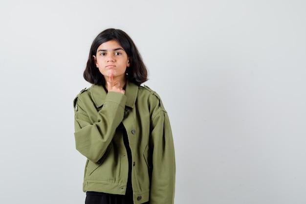 Девушка в футболке, зеленой куртке, держа палец на подбородке и внимательно глядя, вид спереди.