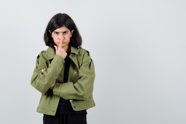 Девушка в футболке, зеленой куртке, держа палец на носу и внимательно глядя, вид спереди.