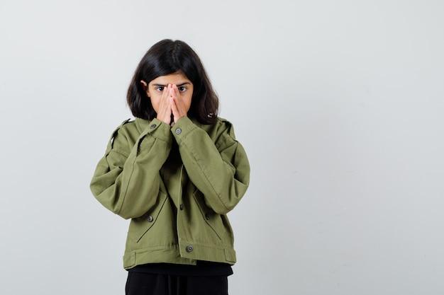 Девушка в футболке, зеленой куртке, держась за рот и внимательно глядя, вид спереди.