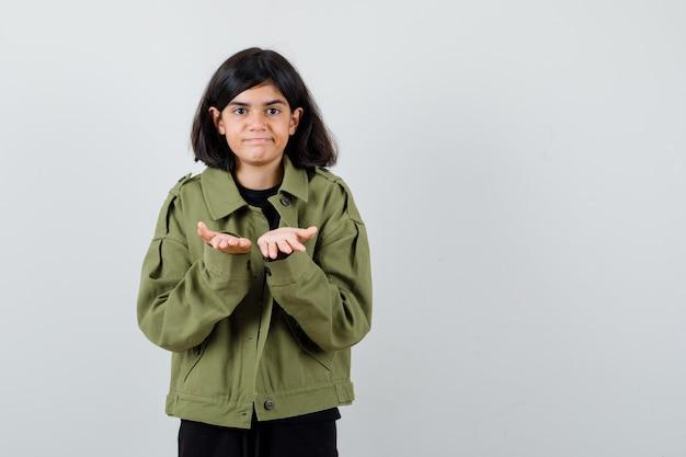 Девушка-подросток в футболке, зеленой куртке, давая или получая жест и выглядя довольной, вид спереди.