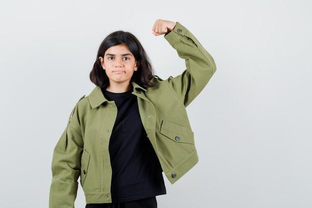 Tシャツ、腕の筋肉を示し、自信を持って見える緑色のジャケットの10代の少女、正面図。