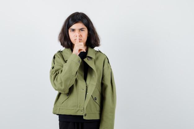 Tシャツを着た10代の少女、沈黙のジェスチャーを示し、注意深く見ている緑のジャケット、正面図。