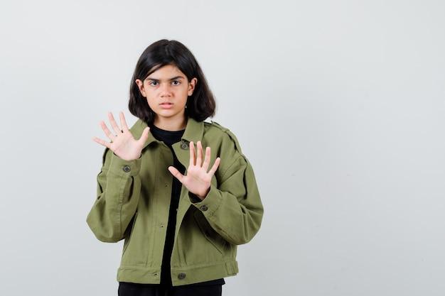 Tシャツを着た10代の少女、停止ジェスチャーを示し、自信を持って見える緑色のジャケット、正面図。