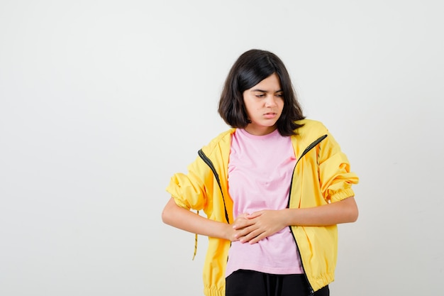 Tシャツを着た10代の少女、お腹に手を置いて痛みを伴うジャケット、正面図。
