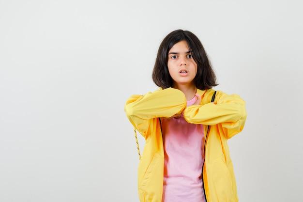 Tシャツを着た10代の少女、自分を指してショックを受けたジャケット、正面図。