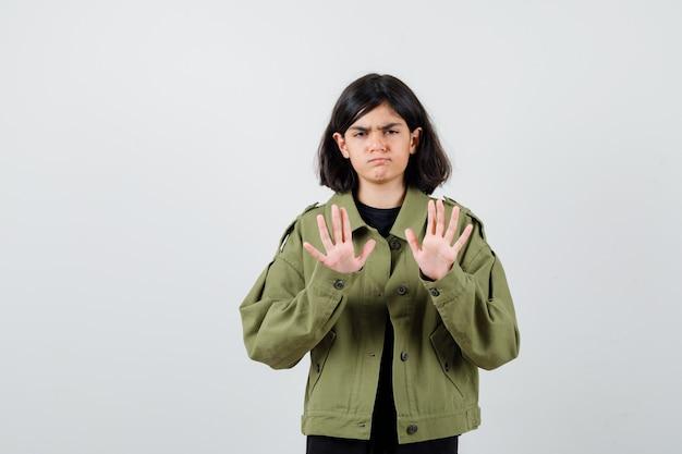 티셔츠를 입은 10대 소녀, 정지 제스처를 보여주고 불만족스러워 보이는 재킷, 전면 보기.