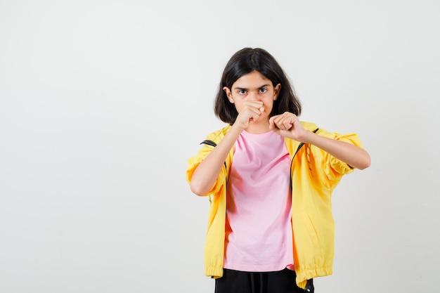 Девушка в футболке, куртка, стоящая в позе боя и смотрящая сосредоточенно, вид спереди.