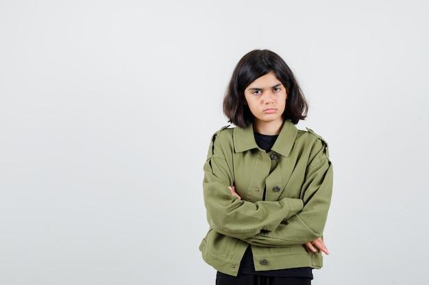 티셔츠를 입은 10대 소녀, 팔짱을 끼고 서 있는 재킷과 무모한 앞모습.