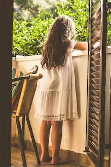 Девушка в белом платье и с длинными каштановыми волосами стоит на балконе на фоне сада