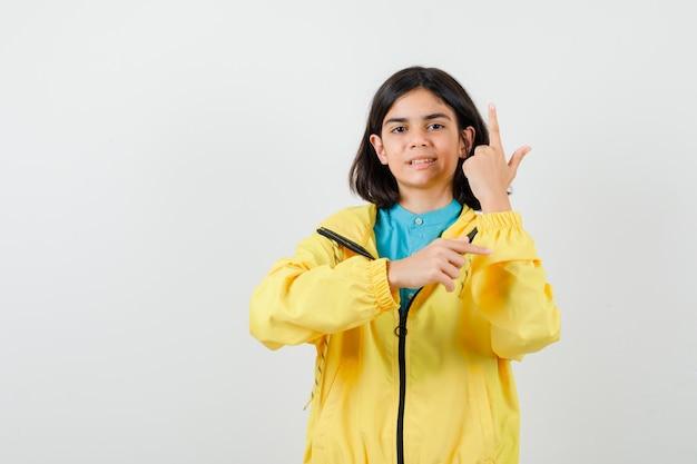 노란색 재킷을 입은 10대 소녀가 손가락을 위아래로 가리키고 유쾌한 모습을 하고 있습니다.