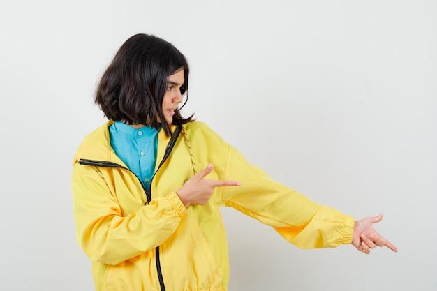 Девушка в желтой куртке, указывая направо и глядя, вид спереди.