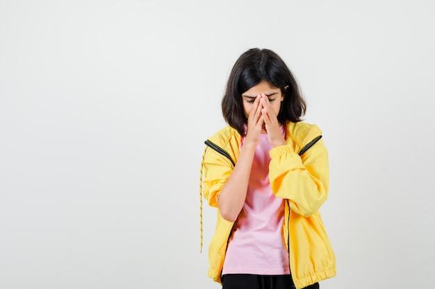 黄色のトラックスーツを着た10代の少女、顔に手をつないで、動揺して見えるtシャツ、正面図。