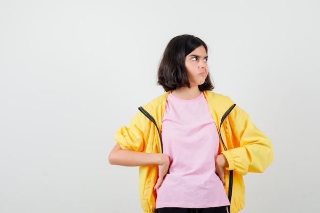 黄色のトラックスーツを着た10代の少女、腰に手をつないで、横を見て、不満を見て、正面図のtシャツ。
