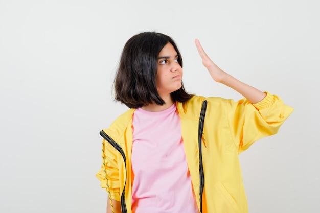 黄色のトラックスーツを着た10代の少女、顔の近くに手のひらを持って不機嫌そうに見えるtシャツ、正面図。