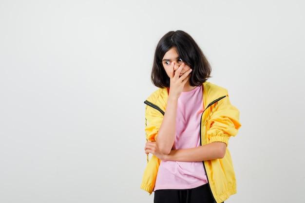 Tシャツ、ジャケットで顔に手を保ち、困惑しているように見える10代の少女。正面図。