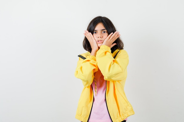 Ragazza teenager che tiene le mani sulle guance in maglietta, giacca gialla e sembra perplessa. vista frontale.