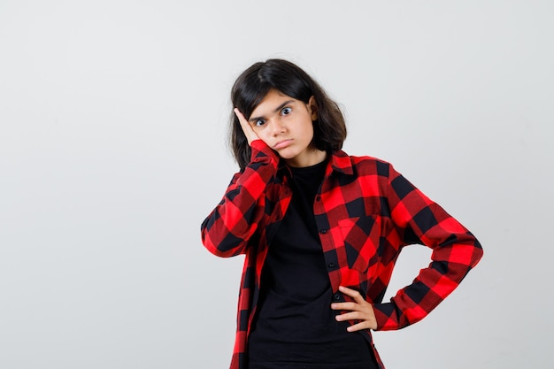 Teen girl leaning cheek on hand in t-shirt, checkered shirt and looking puzzled , front view. Premium Photo