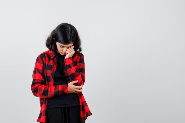 Девушка-подросток, опираясь щекой на кулак в футболке, клетчатой рубашке и выглядела усталой. передний план. Бесплатные Фотографии