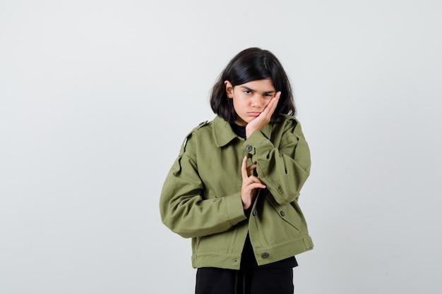 Ragazza teenager che si appoggia la guancia sul palmo in giacca verde e sembra stanca, vista frontale.