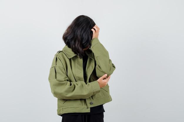 Tシャツ、緑のジャケットで手に頭をもたれ、悲しそうに見える10代の少女。正面図。