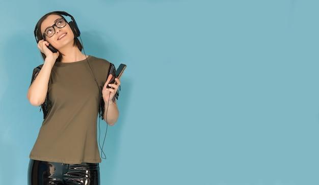 헤드폰으로 그녀의 휴대 전화에서 음악을 듣고 십 대 소녀