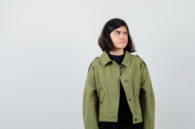 Teen girl looking aside while curving lips in army green jacket and looking displeased , front view.