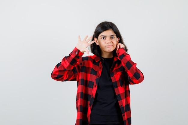 Ragazza teenager che guarda l'obbiettivo mentre mostra palmo in t-shirt, camicia a scacchi e guardando fiducioso, vista frontale.